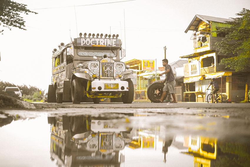Jeepney Gang Alumni Portal - Jeepney - A man with a spare tire and a parked jeepney.